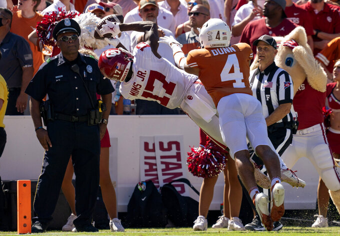 Oklahoma wide receiver Marvin Mims (17) makes a diving catch for a touchdown in front of Texas defensive back Darion Dunn (4) during the fourth quarter of an NCAA college football game at the Cotton Bowl, Saturday, Oct. 9, 2021, in Dallas. (AP Photo/Jeffrey McWhorter)