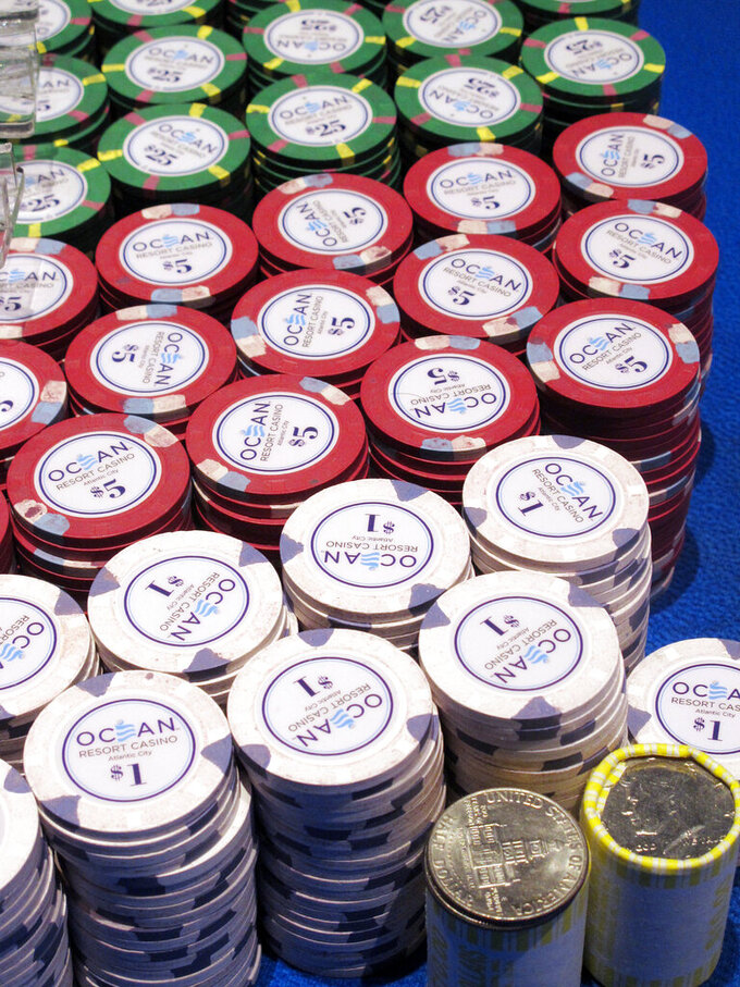 In this June 18, 2019 photo, gambling chips sit on a a gaming table at the Ocean Casino Resort in Atlantic City, N.J. How to keep chips clean is one of many issues with which U.S. casinos are grappling as they prepare to reopen after shutdowns due to the coronavirus outbreak. (AP Photo/Wayne Parry)
