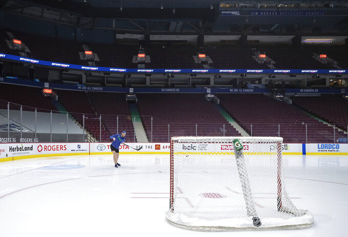 Vancouver Canucks goalie Thatcher Demko walks on the ice and shoots a puck around after the team's NHL hockey game against the Calgary Flames was postponed due to a positive COVID-19 test result in Vancouver, British Columbia, Wednesday, March 31, 2021. (Darryl Dyck/The Canadian Press via AP)