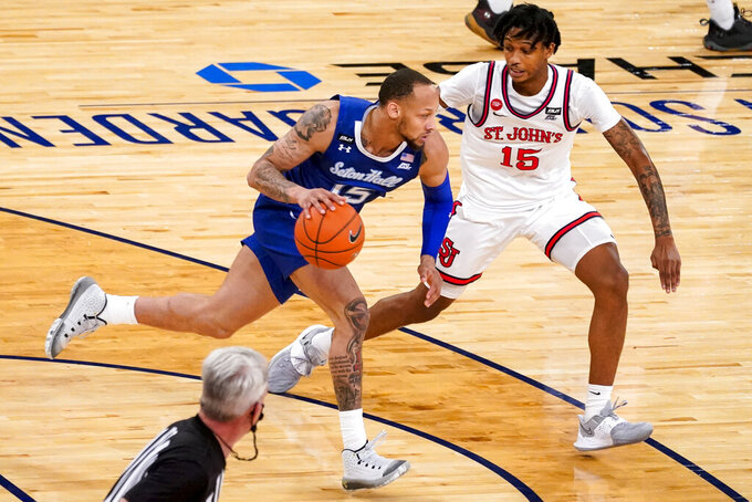 Seton Hall guard Takal Molson, foreground, drives up court against St. John's guard Vince Cole (15) during the second half of an NCAA college basketball game in the quarterfinals of the Big East conference tournament, Thursday, March 11, 2021, in New York. (AP Photo/Mary Altaffer)