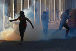 An anti-government protester prepares to throw a tear gas canister fired by Iraq security forces during clashes in the al-Rasheed street in Baghdad, Iraq, Friday, Nov. 8, 2019. The demonstrators complain of widespread corruption, lack of job opportunities and poor basic services, including regular power cuts despite Iraq's vast oil reserves. They have snubbed limited economic reforms proposed by the government, calling for it to resign. (AP Photo/Khalid Mohammed)