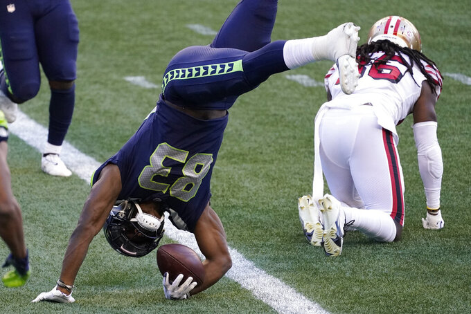 Seattle Seahawks wide receiver David Moore upends himself as he gets up after scoring a touchdown against the San Francisco 49ers during the second half of an NFL football game, Sunday, Nov. 1, 2020, in Seattle. (AP Photo/Elaine Thompson)