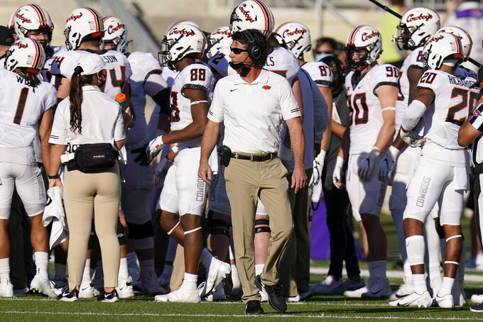 Oklahoma State head coach Mike Gundy, center, paces the sideline during the first half of an NCAA college football game against Kansas State in Manhattan, Kan., Saturday, Nov. 7, 2020. (AP Photo/Orlin Wagner)