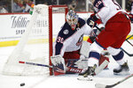 Columbus Blue Jackets goaltender Elvis Merzlikins (90) deflects the puck with Blue Jackets defenseman David Savard (58) in front of him during the second period of the team's NHL hockey game against the New Jersey Devils, Sunday, Feb. 16, 2020, in Newark, N.J. (AP Photo/Kathy Willens)