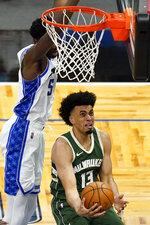 Milwaukee Bucks forward Jordan Nwora, right, goes past Orlando Magic center Mo Bamba, left, for a shot during the second half of an NBA basketball game, Sunday, April 11, 2021, in Orlando, Fla. (AP Photo/John Raoux)