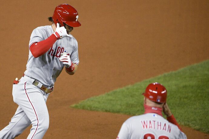 Philadelphia Phillies' Bryce Harper, left, celebrates his home run with third base coach Dusty Wathan during the sixth inning of the team's baseball game against the Washington Nationals, Wednesday, Sept. 23, 2020, in Washington. This was Harper's second homer of the night. (AP Photo/Nick Wass)