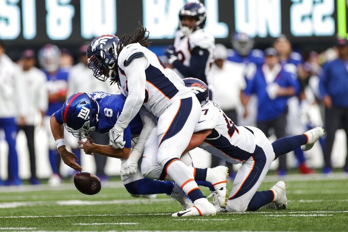 New York Giants quarterback Daniel Jones (8) fumbles the ball as Denver Broncos' A.J. Johnson (45) tackles him during the second half of an NFL football game Sunday, Sept. 12, 2021, in East Rutherford, N.J. The Broncos recovered the ball on the play. The Broncos won 27-13. (AP Photo/Adam Hunger)