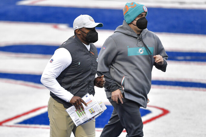 Miami Dolphins head coach Brian Flores, left, takes the field before the first half of an NFL football game against the Buffalo Bills, Sunday, Jan. 3, 2021, in Orchard Park, N.Y. (AP Photo/Adrian Kraus)