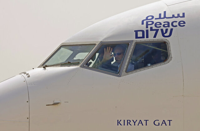The captain of the El Al airliner which will carry US and Israeli delegations to the United Arab Emirates waves to spectators as the plane prepares to take off on the first-ever commercial flight from Israel to the UAE, at Ben Gurion Airport near Tel Aviv, Israel, Monday, Aug. 31, 2020. (Menahem Kahana/Pool via AP)