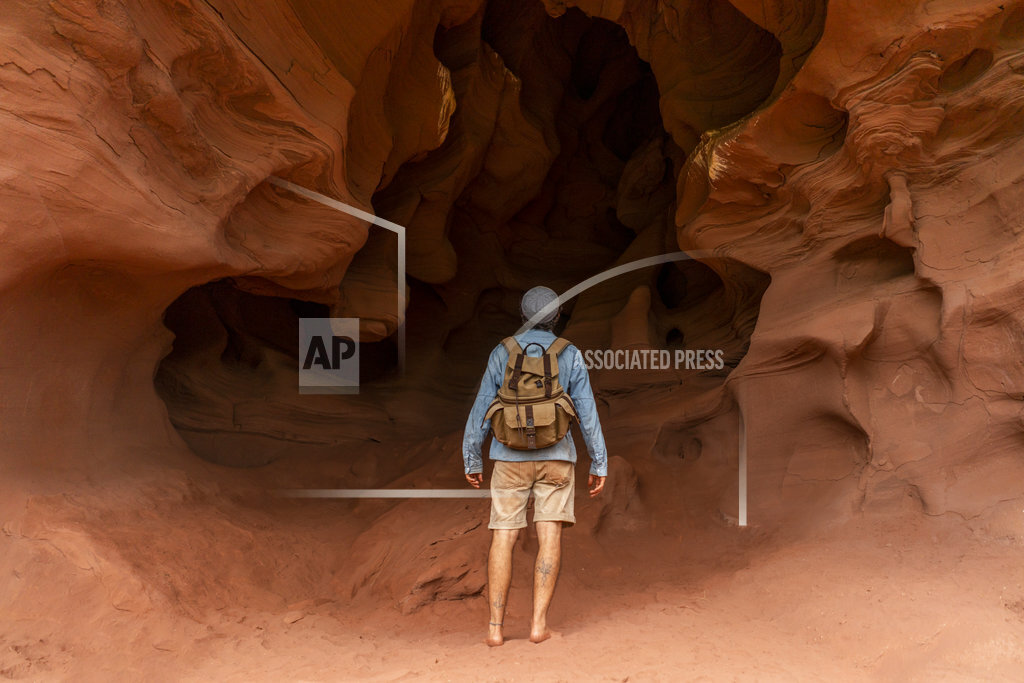 Young man with backpack, looking at cave, rear view