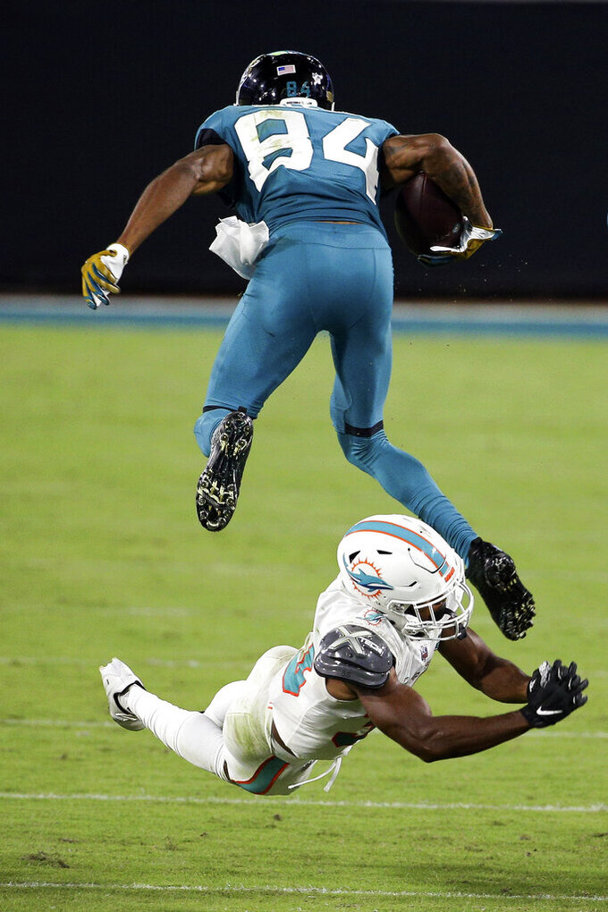 Jacksonville Jaguars wide receiver Keelan Cole (84) leaps over Miami Dolphins cornerback Jamal Perry during the second half of an NFL football game, Thursday, Sept. 24, 2020, in Jacksonville, Fla. (AP Photo/Stephen B. Morton)