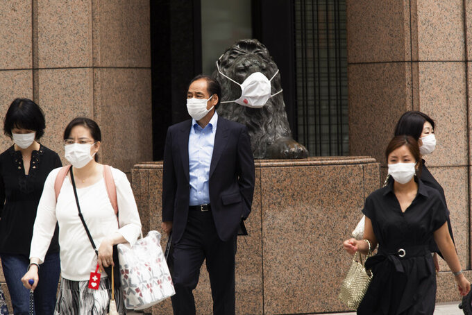 People wearing face masks walk across a traffic intersection, passing by a statue of a lion with a face mask displayed at a department store in the famed Ginza shopping neighborhood in Tokyo on Friday, May 21, 2021. Japan has approved the use of two new vaccines - Moderna and AstraZeneca - hours ahead of an expansion of a state of coronavirus emergency that will cover roughly 40% of the population. It's the latest effort to contain a worrying surge in infections nine weeks ahead of the opening of the Tokyo Olympics.(AP Photo/Hiro Komae)