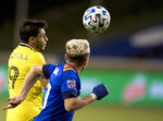 Columbus Crew defender Milton Valenzuela (19) heads the ball as FC Cincinnati forward Kekuta Manneh (31) presses him during the first half of an MLS soccer match Wednesday, Oct. 14, 2020, in Cincinnati. (Albert Cesare/The Cincinnati Enquirer via AP)