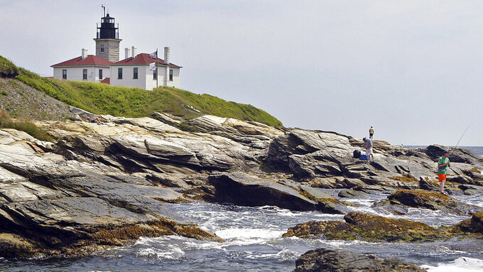 FILE - In this July 7, 2006, file photograph, fishermen cast on the rocky shore at the Beavertail Lighthouse, the third-oldest lighthouse in America, at the tip of Beavertail State Park, on Narragansett Bay, in Jamestown, R.I. The federal government's General Services Administration announced the U.S. Coast Guard has decided it no longer needs four of the nation's most storied and picturesque lighthouses, including the Beavertail Lighthouse. The government says it'll make the historic lighthouses and their outbuildings available at no cost to federal, state and local agencies; nonprofit organizations; educational and community development agencies; or groups devoted to parks, recreation, culture, or historic preservation. (AP Photo/Stew Milne, File)
