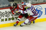 New York Rangers' Ryan Lindgren, right, pushes New Jersey Devils' Jack Hughes into the boards during the first period of the NHL hockey game in Newark, N.J., Sunday, April 18, 2021. (AP Photo/Seth Wenig)