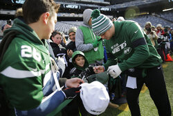 New York Jets quarterback Sam Darnold, right, signs autographs before an NFL football game against the Miami Dolphins, Sunday, Dec. 8, 2019, in East Rutherford, N.J. (AP Photo/Seth Wenig)