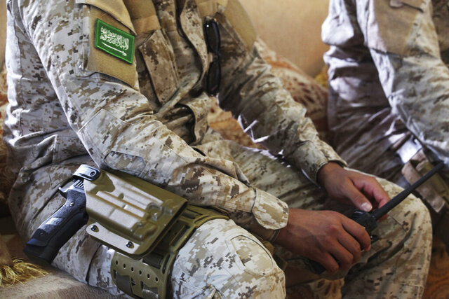 FILE - In this Nov. 28, 2018 file photo, an armed Saudi soldier holds a walkie-talkie near Mukalla, Yemen, at an airport now serving as a military base for the United Arab Emirates. In a new report released Wednesday, March 25, 2020, Human Rights Watch accused Saudi Arabia of committing grave abuses against civilians in an eastern province of Yemen over the past year, including torture, forced disappearances and detention. The New York-based watchdog presented chilling testimony from former detainees in Yemen's remote eastern province of al-Mahrah, which borders Saudi Arabia and Oman. (AP Photo/Jon Gambrell, File)