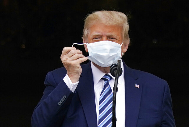 With two bandages on his hand, President Donald Trump removes his face mask to speak from the Blue Room Balcony of the White House to a crowd of supporters, Saturday, Oct. 10, 2020, in Washington. (AP Photo/Alex Brandon)