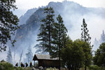 In this  June 11, 2019 photo, firefighters prepare to protect Knapp's Cabin, a storage shed from the 1920s that is the oldest building in Cedar Grove, during a prescribed burn at Kings Canyon National Park, Calif. The prescribed burn, a low-intensity, closely managed fire, was intended to clear out undergrowth and protect the heart of Kings Canyon National Park from a future threatening wildfire. The tactic is considered one of the best ways to prevent the kind of catastrophic destruction that has become common, but its use falls woefully short of goals in the West. (AP Photo/Brian Melley)