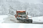 A snowplow clears the snow from Route 9, in Marlboro, Vt., as several inches of snow falls on Friday, April 16, 2021.  (Kristopher Radder/The Brattleboro Reformer via AP)