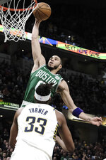 Boston Celtics forward Jayson Tatum (0) goes up to dunk in front of Indiana Pacers center Myles Turner (33) during the second half of an NBA basketball game in Indianapolis, Tuesday, March 10, 2020.(AP Photo/AJ Mast)