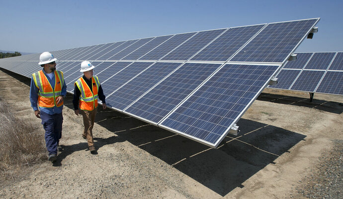 FILE - In this Thursday, Aug. 17, 2017, file photo, solar tech Joshua Valdez, left, and senior plant manager Tim Wisdom walk past solar panels at a Pacific Gas and Electric Solar Plant, in Dixon, Calif.  U.S. wholesale prices edged up a slight 0.1% in August 2019 as energy prices took a big plunge, a further sign that inflation is remaining tame. The Labor Department  says the gain in its producer price index, which measures inflation pressures before they reach the consumer, followed a modest 0.2% rise in July. Core inflation, which excludes food and energy, was up a stronger 0.3%.  (AP Photo/Rich Pedroncelli, File)
