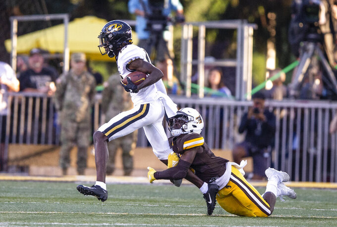 Wyoming defender Rome Weber tackles Missouri's Kam Scott during the first half an NCAA college football game Saturday, Aug. 31, 2019, in Laramie, Wyo. (AP Photo/Michael Smith)