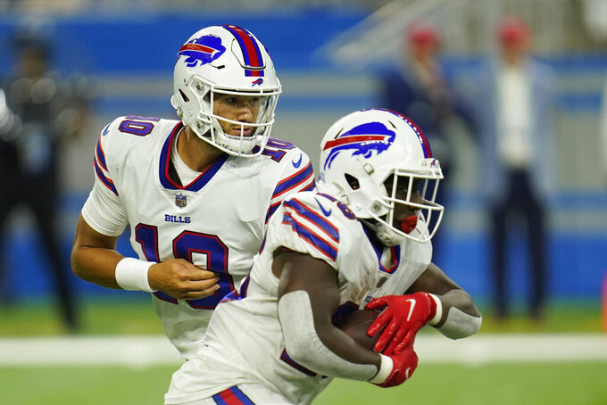 Buffalo Bills quarterback Mitchell Trubisky (10) hands off to running back Devin Singletary during the first half of a preseason NFL football game against the Detroit Lions, Friday, Aug. 13, 2021, in Detroit. (AP Photo/Paul Sancya)