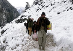Kashmiri villagers walk through snow-covered road after heavy snowfall in Neelum Valley, Pakistan-administered Kashmir, Wednesday, Jan. 15, 2020. Search teams aided by Pakistani troops pulled out 21 more bodies from homes destroyed by this week's avalanches in the disputed Himalayan region of Kashmir, raising the overall death toll due to severe winter weather to more than 155 for Pakistan and Afghanistan, officials said. (AP Photo/Abdul Razaq)