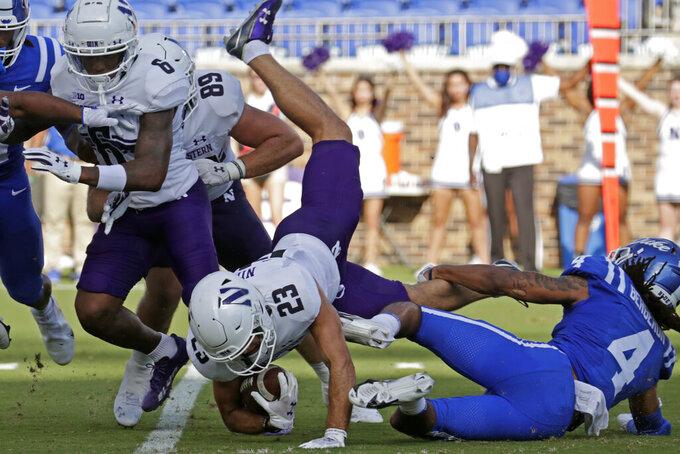 Northwestern wide receiver Raymond Niro III (23) is tripped by Duke cornerback Cameron Bergeron (4) as he runs upfield during the first half of an NCAA college football game in Durham, N.C., Saturday, Sept. 18, 2021. (AP Photo/Chris Seward)