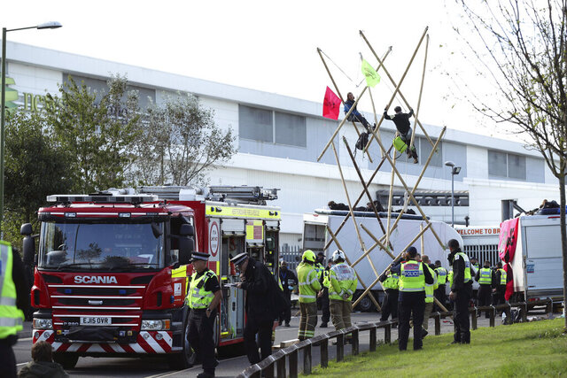 Police and fire services at the scene, outside Broxbourne newsprinters as protesters continue to block the road, in Broxbourne, Hertfordshire, England, Saturday, Sept. 5, 2020. Environmental activists have blockaded two British printing plants, disrupting the distribution of several national newspapers. The group Extinction Rebellion said it targeted printworks at Broxbourne, north of London, and Knowsley in northwest England that are owned by Rupert Murdoch's News Corp. Dozens of protesters locked themselves to vehicles and bamboo scaffolding to block the road outside the plants. The facilities print Murdoch-owned papers The Sun and The Times, as well as the Daily Telegraph, the Daily Mail and the Financial Times. (Yui Mok/PA via AP)