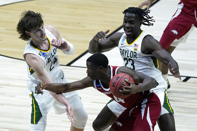 Arkansas guard Davonte Davis (4) tries to get past Baylor guard Matthew Mayer (24) and forward Jonathan Tchamwa Tchatchoua (23) during the second half of an Elite 8 game in the NCAA men's college basketball tournament at Lucas Oil Stadium, Monday, March 29, 2021, in Indianapolis. (AP Photo/Darron Cummings)