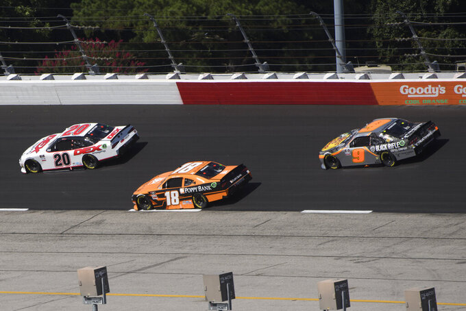 Daniel Hemric (18) is passed by Harrison Burton (20) as Noah Gragson (9) bears in during the first stage of a NASCAR Xfinity Series auto race Saturday, Sept. 4, 2021, in Darlington, S.C. (AP Photo/John Amis)