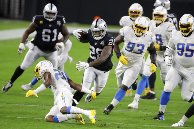 Las Vegas Raiders running back Josh Jacobs (28) runs against the Los Angeles Chargers during the first half of an NFL football game, Thursday, Dec. 17, 2020, in Las Vegas. (AP Photo/Isaac Brekken)
