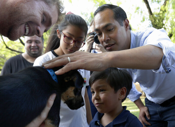 Democratic presidential candidate and former Housing Secretary Julian Castro, right, with his son Cristian, and daughter Carina, visit with Ivan, a puppy up for adoption, during a stop at the Animal Defense League of Texas shelter, Monday, Aug. 19, 2019, in San Antonio. (AP Photo/Eric Gay)