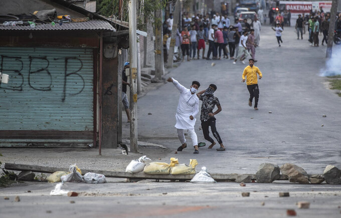 Kashmiri protesters throw stones on Indian paramilitary soldiers and policemen amid tear smoke during a clash in Srinagar, Indian controlled Kashmir, Thursday, Sept. 2, 2021. Indian authorities cracked down on public movement and imposed a near-total communications blackout in disputed Kashmir on Thursday after the death of Syed Ali Geelani, a top separatist leader who became the emblem of the region's defiance against New Delhi. (AP Photo/ Mukhtar Khan)