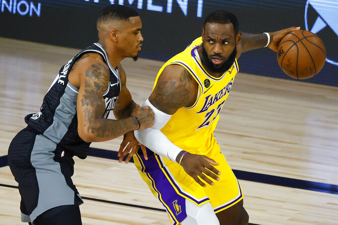 Sacramento Kings' DaQuan Jeffries, left, defends against Los Angeles Lakers' LeBron James during the second quarter of an NBA basketball game Thursday, Aug. 13, 2020, in Lake Buena Vista, Fla. (Kevin C. Cox/Pool Photo via AP)