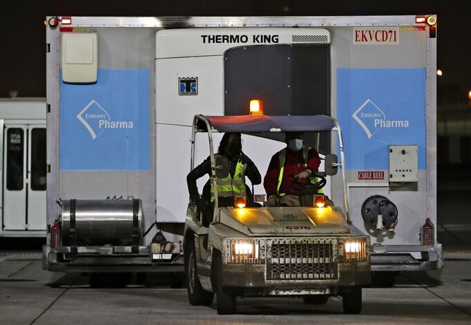 A shipment of Pfizer-BioNTech COVID-19 coronavirus vaccines is moved inside a temperature-controlled container after being offloaded from an Emirates Airlines Boing 777 that arrived from Brussels to Dubai International Airport in Dubai, United Arab Emirates, early Sunday, Feb. 21, 2021. As the coronavirus pandemic continues to clobber the aviation industry, Emirates Airlines, the Middle East's biggest airline, is seeking to play a vital role in the global vaccine delivery effort. (AP Photo/Kamran Jebreili)