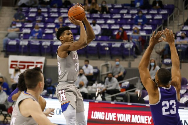 Kansas guard Ochai Agbaji (30) shoots as TCU forward Jaedon LeDee (23) defends during the first half of an NCAA college basketball game in Fort Worth, Texas, Tuesday, Jan. 5, 2021. (AP Photo/Ron Jenkins)