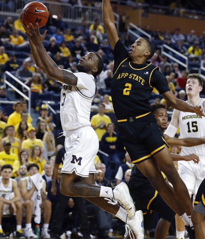 Michigan guard Zavier Simpson (3) makes a layup as Appalachian State forward Kendall Lewis (2) defends during the second half of an NCAA college basketball game, Tuesday, Nov. 5, 2019, in Ann Arbor, Mich. (AP Photo/Carlos Osorio)