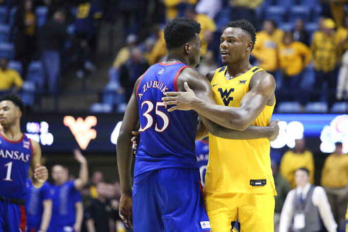 Kansas center Udoka Azubuike (35) and West Virginia forward Oscar Tshiebwe (34) greet each other after an NCAA college basketball game Wednesday, Feb. 12, 2020, in Morgantown, W.Va. (AP Photo/Kathleen Batten)
