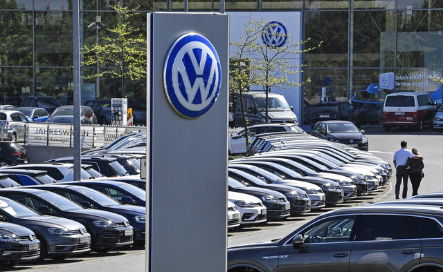 In this April 20, 2020 file photo, a Volkswagen car dealer is open in Essen, Germany. In times when a pandemic unleashes death and poverty, the concept of what is essential to keep society functioning in a lockdown is gripping Europe. What may stay open in one country may be designated as non-essential just across the border. (AP Photo/Martin Meissner, File)