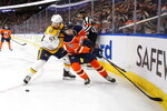 Nashville Predators' Dante Fabbro (57) and Edmonton Oilers' Kailer Yamamoto (56) battle for the puck during second period NHL hockey action in Edmonton, Alberta, Tuesday, Jan. 14, 2019. (Jason Franson/The Canadian Press via AP)