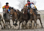 Riders compete during a kok boru, also called ulak tartysh, a traditional game in which players on horseback manoeuvre with a goat's carcass and score by putting it into the opponents' goal outside Sokuluk village, 20 km (12,5 miles) west of Bishkek, Kyrgyzstan, Tuesday, March 30, 2021. (AP Photo/Vladimir Voronin)