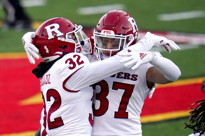 Rutgers defensive backs Rani Abdulaziz (32) and Joe Lusardi (37) react after Rutgers defeated Maryland 27-24 in overtime of an NCAA college football game, Saturday, Dec. 12, 2020, in College Park, Md. (AP Photo/Julio Cortez)