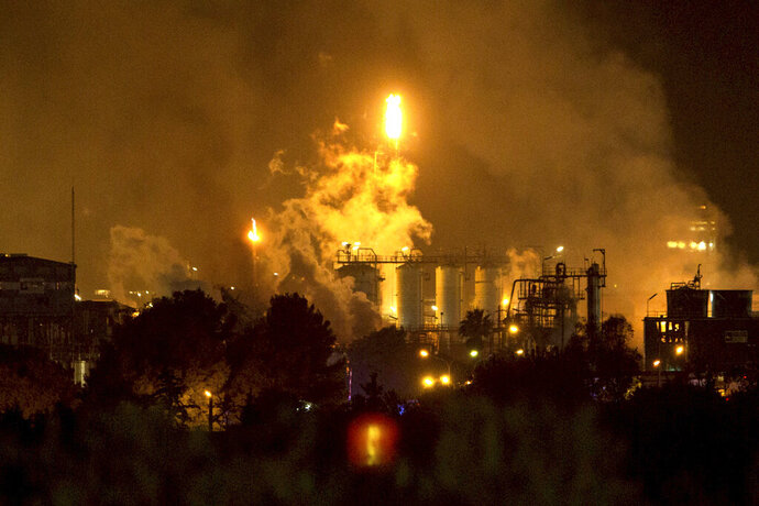 Smoke rise following a big explosion at an industrial hub near the port city of Tarragona, Spain, Tuesday, Jan. 14, 2020. A chemical emergency alert has been activated in northeastern Spain following a big explosion in an industrial zone near the port city of Tarragona, regional emergency services said Tuesday. (AP Photo/David Oliete)