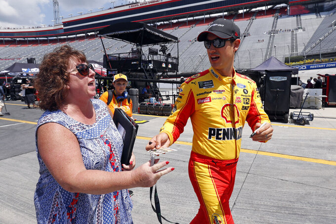 Driver Joey Logano signs an autograph for a fan before practice for an NASCAR Xfinity Series auto race on Thursday, Aug. 15, 2019, in Bristol, Tenn. (AP Photo/Wade Payne)