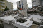 Rescuers stand on a collapsed building in Durres, western Albania, Friday, Nov. 29, 2019. The operation to find survivors and recover bodies from Albania's deadly earthquake was winding down Friday as the death toll climbed to 49. (AP Photo/Visar Kryeziu)