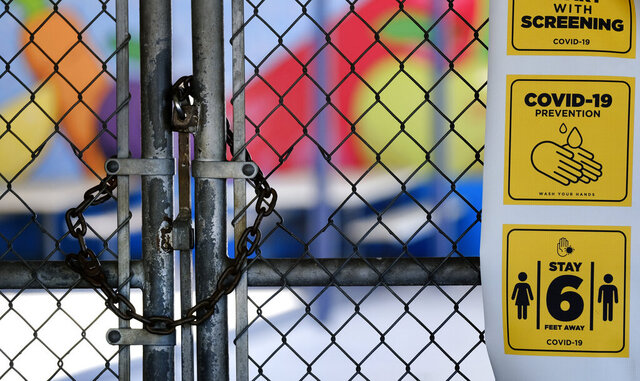 FILE - In this July 13, 2020, file photo, a gate is locked at the closed Ranchito Elementary School in the San Fernando Valley section of Los Angeles. As Gov. Gavin Newsom unveiled details for California elementary schools seeking to reopen with in-person instruction amid the coronavirus pandemic, one of the state's two powerful teachers unions warned that reopening schools would be