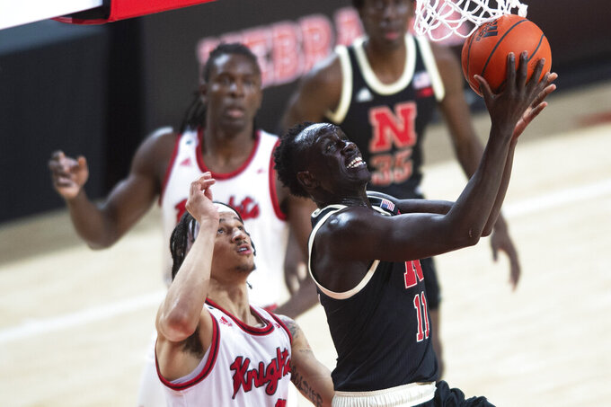 Nebraska's Lat Mayen, right, goes under the basket to score against Rutgers' Caleb McConnell in the first half of an NCAA college basketball game Monday, March 1, 2021, in Lincoln, Neb. (Kenneth Ferriera/Lincoln Journal Star via AP)